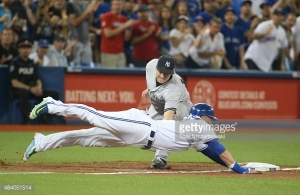 TORONTO, CANADA - AUGUST 14: Josh Donaldson #20 of the Toronto Blue Jays dives back safely to third base in the third inning during MLB game action as Chase Headley #12 of the New York Yankees attempts to make the tag on August 14, 2015 at Rogers Centre in Toronto, Ontario, Canada. (Photo by Tom Szczerbowski/Getty Images) *** Local Caption *** Josh Donaldson; Chase Headley