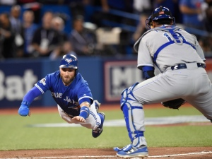 Toronto Blue Jays' Kevin Pillar, left, dives for home plate as he scores in front of Kansas City Royals catcher Salvador Perez during second inning game three American League Championship Series baseball action in Toronto on Monday, Oct. 19, 2015. THE CANADIAN PRESS/Frank Gunn